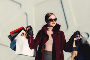 Frau hält weisse und schwarze Einkaufstüten