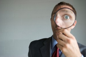 Mann hält eine Lupe vor sein Gesicht