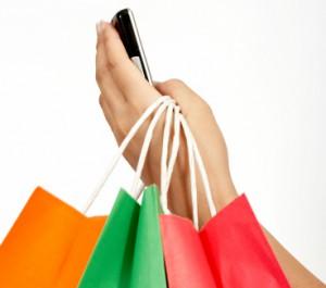 eine Hand mit einem Handy und ein paar Einkaufstüten