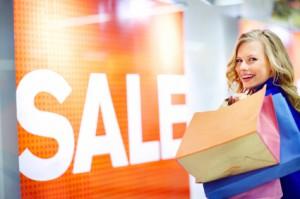 Glückliche junge Frau, welche Einkaufstaschen trägt und vor einem Sale schriftzug steht
