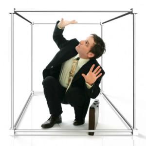 Mann im anzug der in einem Würfel gefangen ist
