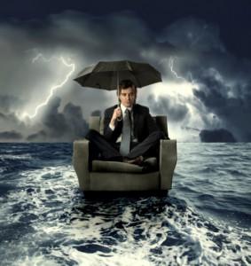 Mann sitzt auf einem Sessel auf dem Meer während eines Sturms
