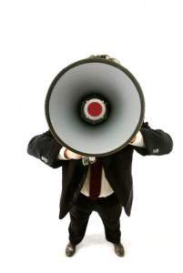 mann mit anzug sagt etwas durch ein megafon