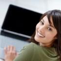 Porträt einer glücklichen jungen Frau, die einen Laptop verwendet