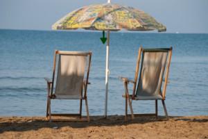 Zwei Holzliegen mit Sonnenschirm am Strand