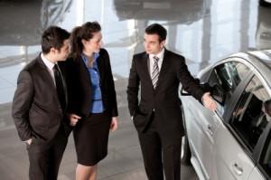 Verkäufer zeigt Leuten ein neues Auto