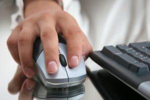 nahaufnahme einer Hand de eine Computermaus bedient