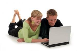 Pärchen schaut sich etwas auf einem Laptop an