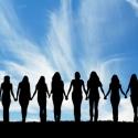 Schattenbild von zehn jungen Frauen, Hand in Hand gehend.