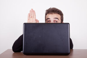 Junger, schüchterner Mann winkt hinter Laptop