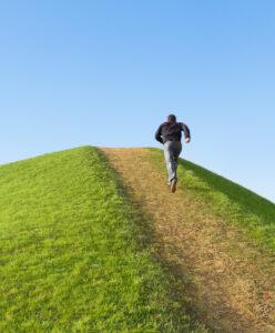 Mann läuft Grasberg hinauf