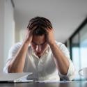 frustrierter junger Geschäftsmann, der zu Hause an einem Laptop arbeitet