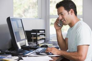 Mann im Innenministerium am Telefon unter Verwendung des Computers und des Lächelns