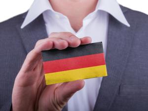 Geschäftsmann ziegt eine Karte mit einer Deutschland Flagge