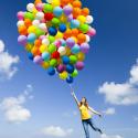 Frau springt mit Ballons