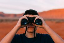 Vision: Junger Mann mit Fernglas