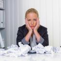 Frau im Büro mit zerknittertem Papier