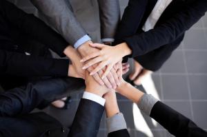 Arbeitsteam legen die Hände aufeinnander als zeichen der Zusammenarbeit