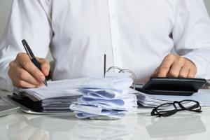 Geschäftsmann füllt Steuern auf einem Schreibtisch aus