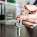 Immobilienmakler, der Hausschlüssel zeigt