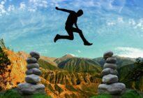 Mann springt in den Bergen über Steine