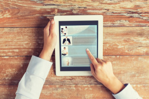 Frau ließt einen Blog auf einem Tablet PC