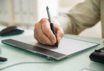 Businessmann, der auf Graphic Tablet schreibt