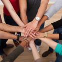 Multiethnische Studenten, die Hände stapeln