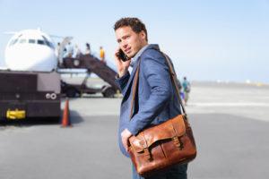 Mann telefoniert neben einem Flugzeug