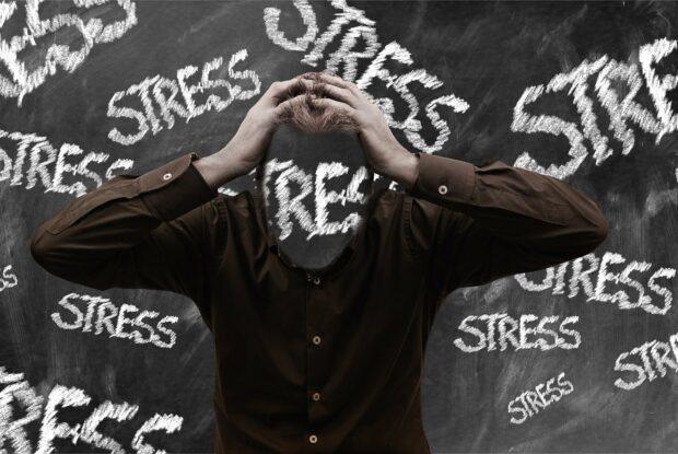 """Mann vor Tafel mit Aufdruck """"Stress"""""""