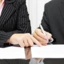 Geschäftsfrau zeigt einem Geschäftsmann wo ein Vertrag zu unterzeichnen ist