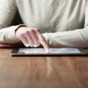 Frauenhand drückt auf digitale Tablette des Schirmes über Holztisch