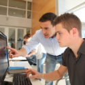 Lehrer und Schüler arbeiten am Computer