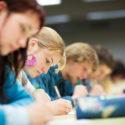 Studentin sitzt in einem Klassenzimmer und absolviert eine Prüfung
