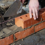 Construction worker laying bricks showing trowel and guideline.