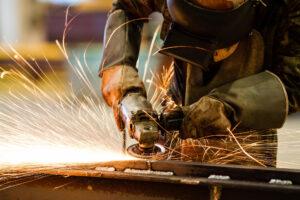 Stahlarbeiter schleift mit dem Winkelschleifer eine Metallschniene