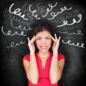 Stress - Frau mit Kopfschmerzen gestresst