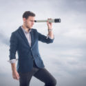 Junger Geschäftsmann, der durch ein Fernglas schaut, um neue Perspektiven zu entdecken.