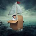 Frau die in einem Papkarton über das Meer segelt
