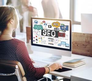 Junge Frau vor Computerbildschirm mit SEO-Screen