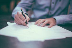 Mann schreibt etwas auf Papier
