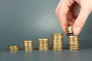 Hand, die Münzen auf Stapel legen