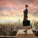 Geschäftsfrau die auf einem Hochhaus steht
