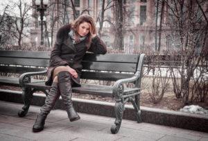 Traurige Frau sitzt auf einer Bank