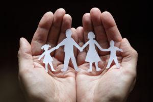 Papierkettenfamilie geschützt in hohlen Händen