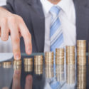 Geschäftsmann-Finger steigen zur Stapel-Münze