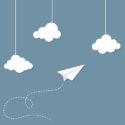 Papierflugzeug zwischen Wolken