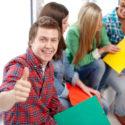Gruppe glückliche Studenten, die sich Daumen zeigen