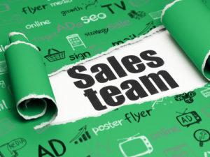 Marketingkonzept: schwarzer Text Sales Team unter einem Stück zerrissenem Papier