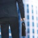 Geschäftsmann mit Aktenkoffer in der Hand auf unscharfem Gebäudehintergrund. Rechtsanwalt und Notar Konzept.